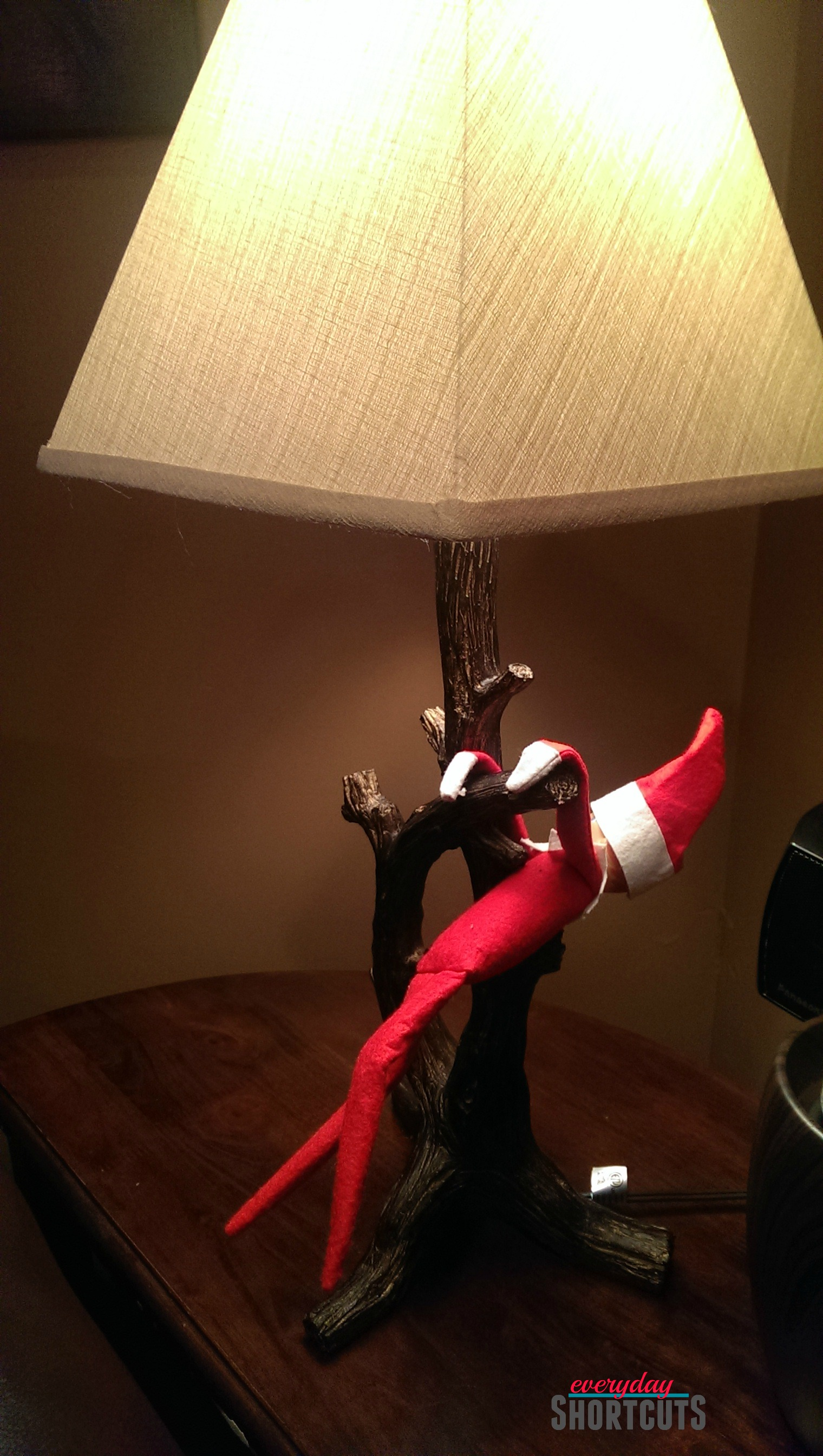 elf on the shelf swinging from lamp